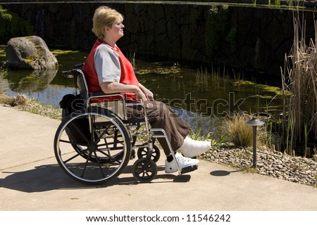 mature woman in wheelchair enjoying the park - stock photo