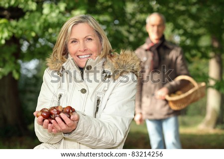 mature woman in woods with husband showing chestnuts - stock photo
