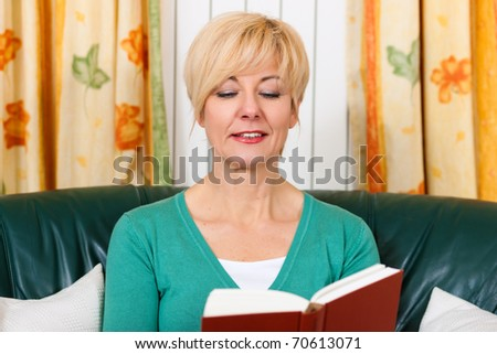 Mature woman is reading a book  at home in her living room