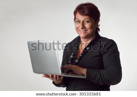 Mature woman isolated on gray background holding a laptop - stock photo