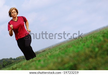 Mature woman jogging in a big summer field. - stock photo