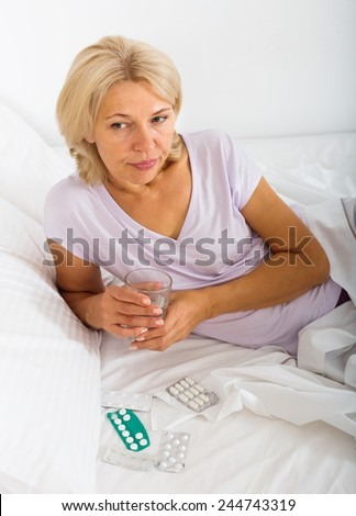 Mature woman laying in bed with pills and glass of water in bedroom - stock photo