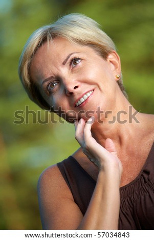 Mature woman leaning on hand and thinking - stock photo