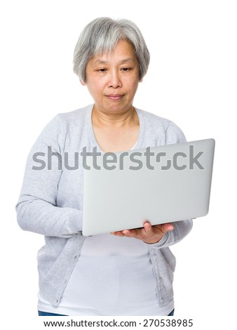 Mature woman learn to use laptop - stock photo