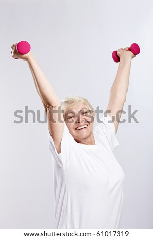 Mature woman lifts weights on a white background