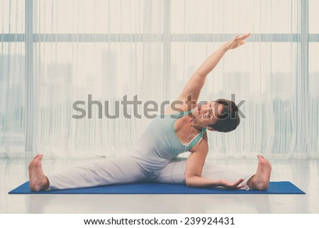 Mature woman listening to the music while doing exercising on the floor - stock photo