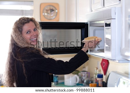 Mature woman loads food into the microwave oven - stock photo