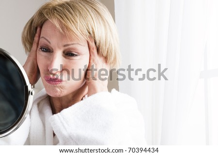 Mature woman looking at herself in the mirror - stock photo