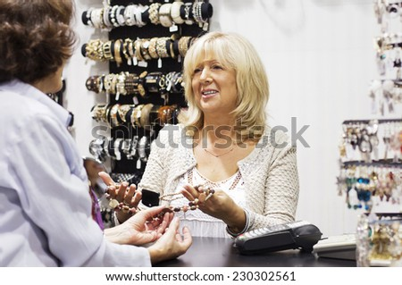 Mature  woman looking at  necklace with her seller. - stock photo