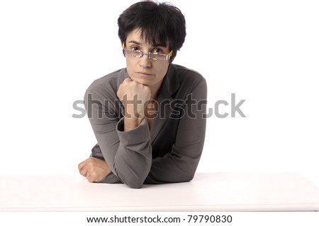 mature woman looking at the camera, head resting on fist - stock photo