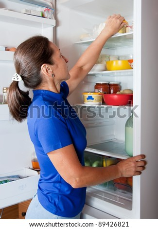 Mature woman looking for something in the fridge at home