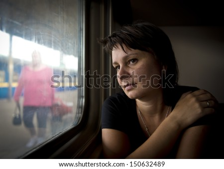 Mature woman looking into window of train. Real people series. - stock photo