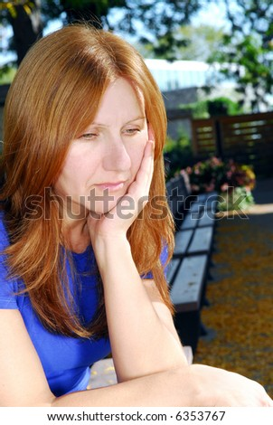 Mature woman looking sad and depressed sitting alone on a park bench - stock photo