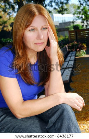 Mature woman looking sad and stressed sitting on a park bench - stock photo