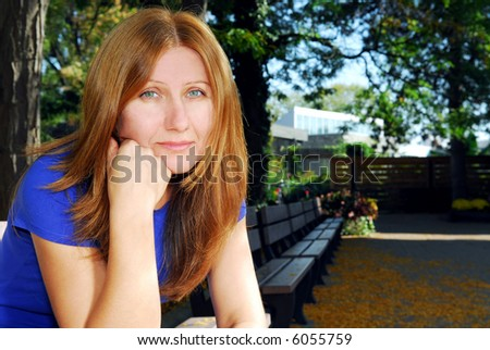 Mature woman looking sad and tired sitting on a park bench - stock photo
