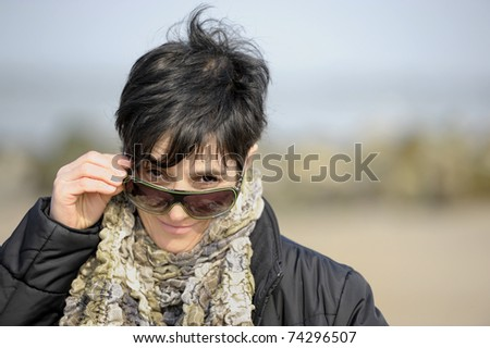 mature woman lookng over her sunglasses - stock photo