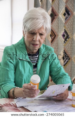 Mature woman looks at her prescription - stock photo