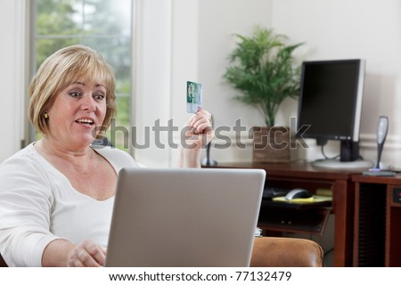 Mature woman looks happy as she shops online - stock photo