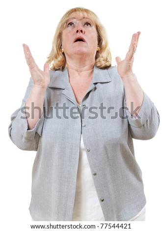 Mature woman looks up with hands raised - stock photo