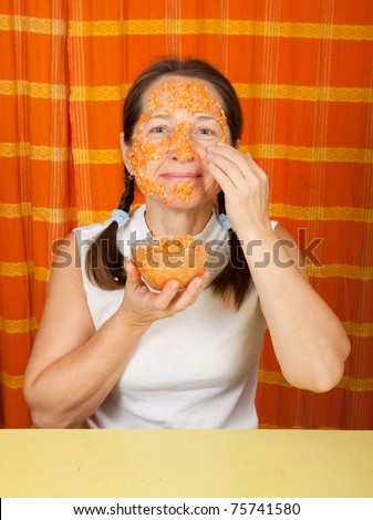 Mature woman making  face-pack from carrot, oatmeal and egg yolk