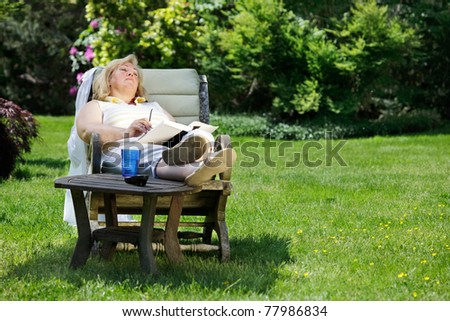 Mature woman napping in a garden chair - stock photo