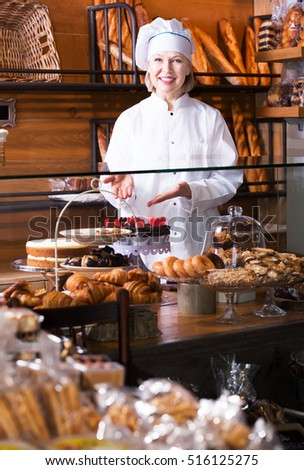 Mature woman offering fancy and sponge cakes for sale in cafe