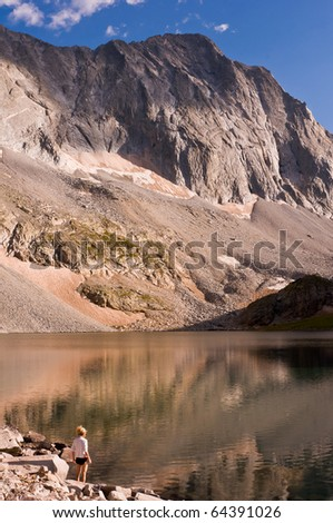 mature woman on the shore of Capitol Lake staring at the massive west face of Capitol Peak - stock photo