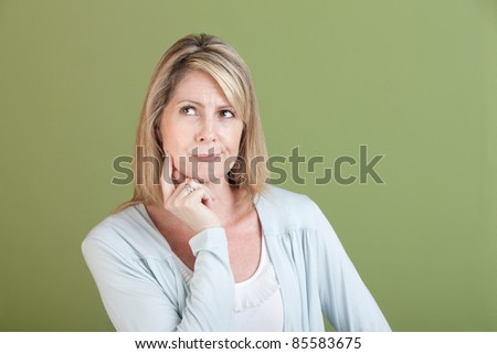 Mature woman over green background with finger on chin