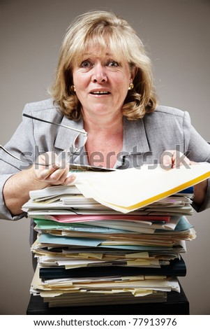 Mature woman overwhelmed by the stack of paperwork - stock photo
