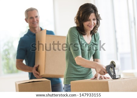Mature woman packing cardboard box with man in background at home - stock photo