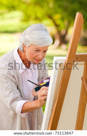 Mature woman painting in the park - stock photo
