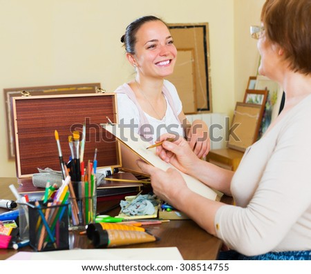 Mature woman paints a portrait of a young girl - stock photo