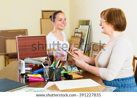 Mature woman paints a portrait of a young happy girl - stock photo