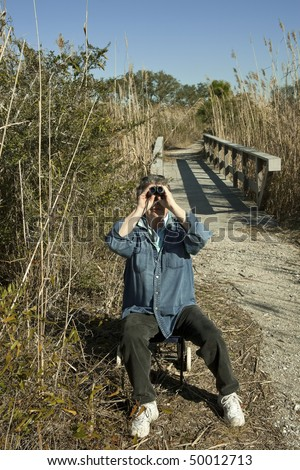 Mature woman peering at the sky through binoculars. On this day she was birdwatching and hiking with all her gear in a national park in Florida's wetlands. - stock photo