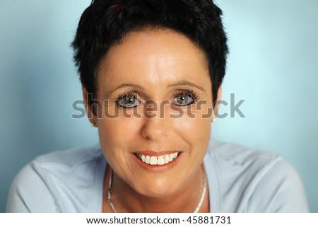 Mature woman portrait  on cyan background - stock photo