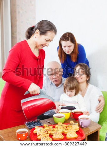 Mature woman pours tea from teapot for three generations family at home