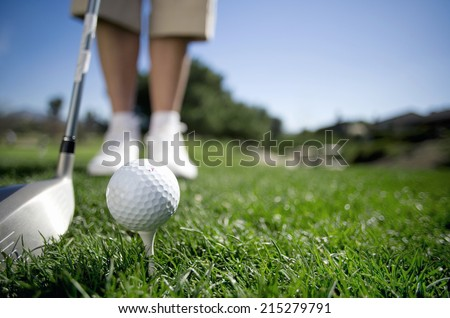 Mature woman preparing to tee off with driver on golf course, close-up, low section, focus on golf ball in foreground (surface level) - stock photo