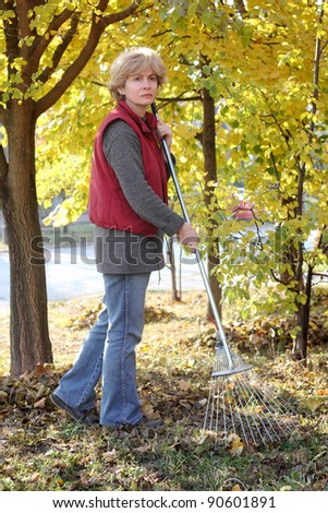 Mature woman raking leaves in a garden