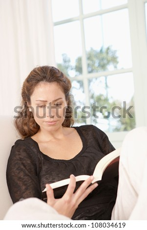 Mature woman reading a book while sitting on a white armchair at home. - stock photo