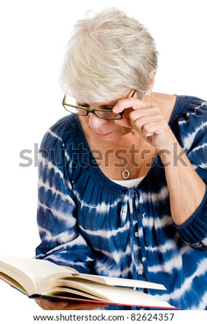 Mature woman reading a book with the help of glasses for her vision. - stock photo
