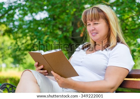 mature woman reading a novel while sitting on a park bench