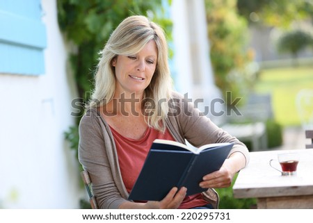 Mature woman reading book in backyard