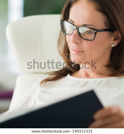Mature Woman Reading Diary, Indoors - stock photo