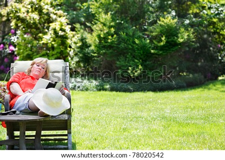 Mature woman reading in a sunny garden chair - stock photo