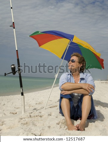 Mature woman relaxing at the beach, waiting for the fish to bite - stock photo