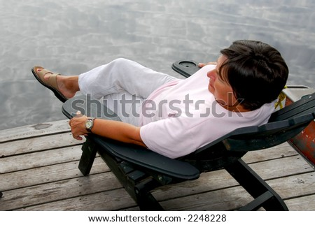 Mature woman relaxing on a pier in a wooden chair