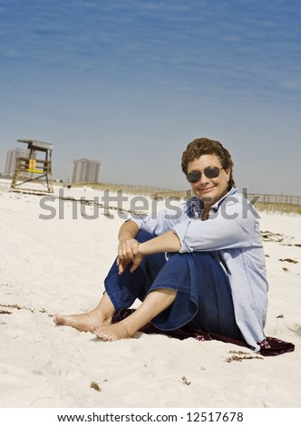 Mature woman relaxing on a sunny white sand beach - stock photo