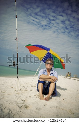Mature woman relaxing on the beach while fishing for pompano