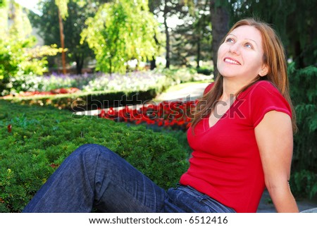 Mature woman relaxing outside in summer park - stock photo