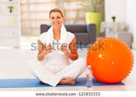 mature woman resting on exercise mat after fitness workout - stock photo